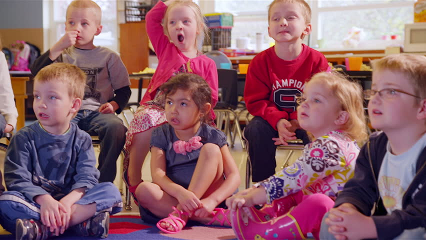 A large group of preschool students sit together and listen for show and tell. Medium shot. | Shutterstock HD Video #4658441