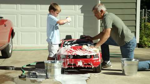 Grandfather and young boy washing car together