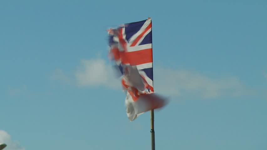 Tattered Union Jack flag flies in wind
