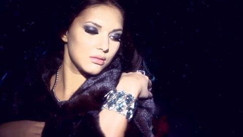Beauty Fashion Model Girl in Mink Fur Coat. Beautiful Woman in Luxury Black Fur Jacket . Winter Fashion, Blowing Hair in the snow. Isolated.
