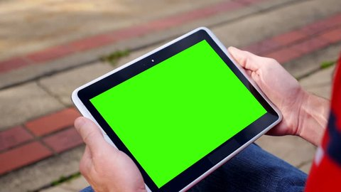 A man holds a blank tablet PC in landscape orientation with a green screen for your own custom content. Optional luma matte and corner markers included for advanced motion tracking.