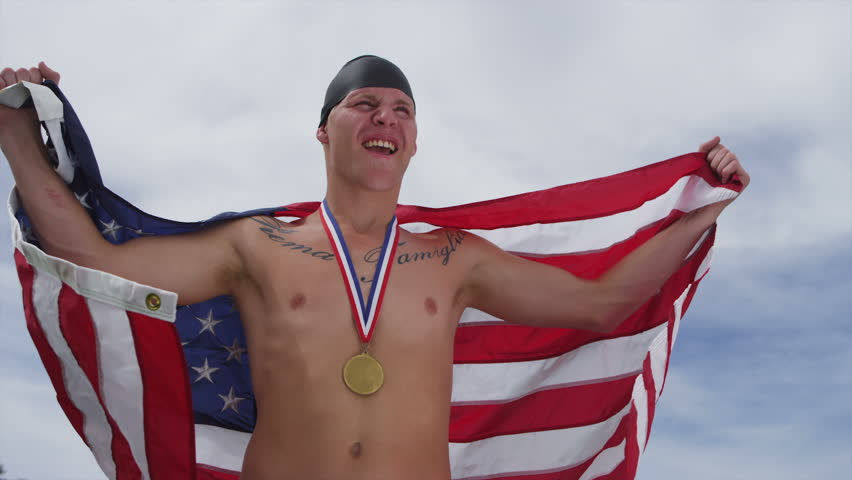Swimmer celebrating with medal and American flag