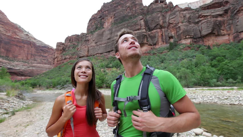 Hikers hiking enjoying view in Zion National park, Utah. Happy interracial couple looking up relaxing after beautiful hike outdoor activity. Mixed race Asian woman and Caucasian man hiker. | Shutterstock HD Video #4687136