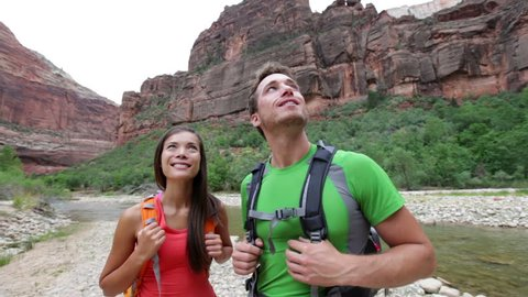 Hikers hiking enjoying view in Zion National park, Utah. Happy interracial couple looking up relaxing after beautiful hike outdoor activity. Mixed race Asian woman and Caucasian man hiker.