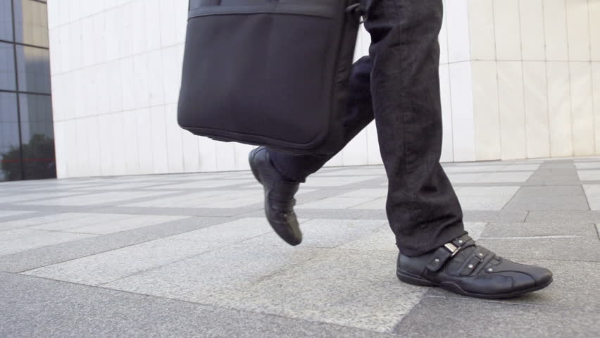 Slow Motion Shot Of A Male Legs Walking. Casually Dressed And Carrying A