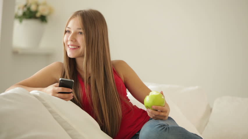 Pretty Girl Sitting On Sofa Holding Apple And Using