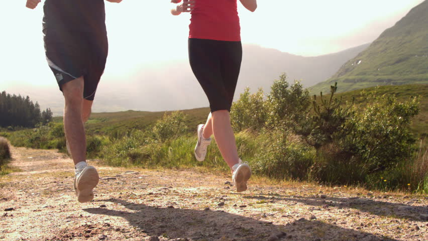 Fit couple jogging on a country trail in slow motion