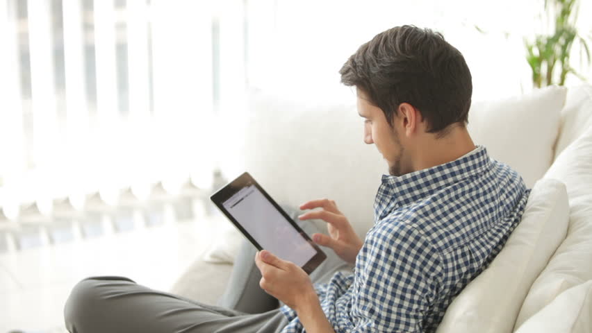 Charming guy sitting on sofa and using touchpad