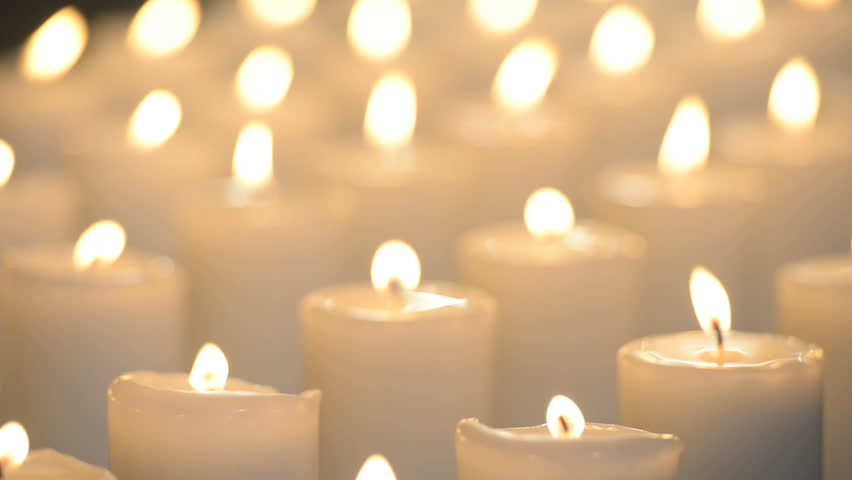 Edited Shot Of White Candles Being Lit Up By A Person And Then Glowing With Soft