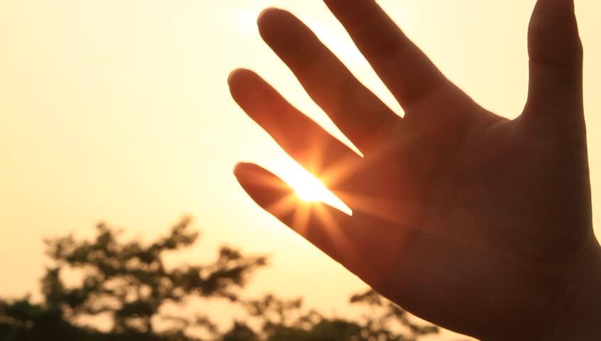 Sunlight through child's fingers