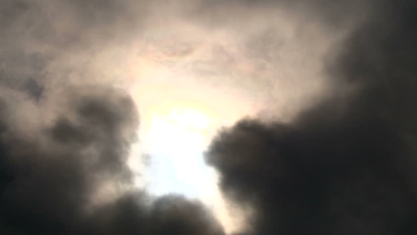 Cloudscape with sun shining behind dark storm clouds, time lapse.