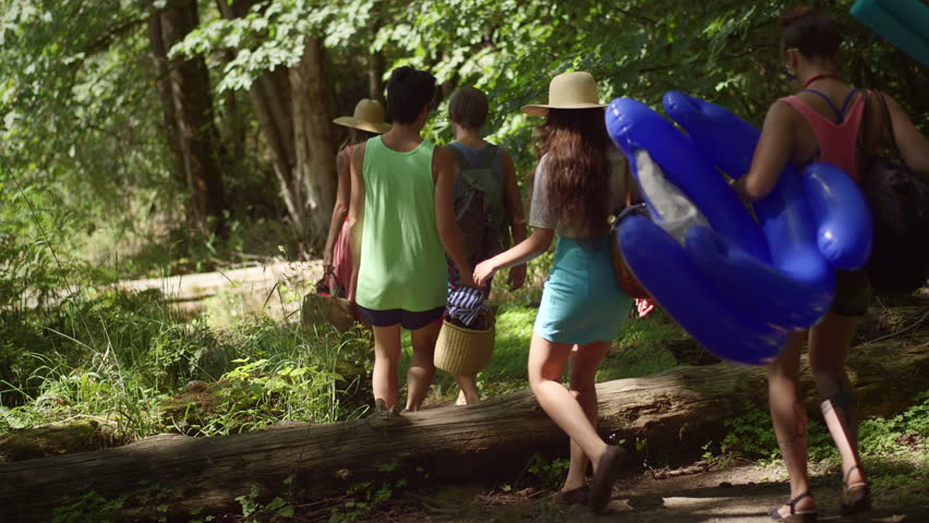 Friends walk through a forest path to get to the beach
