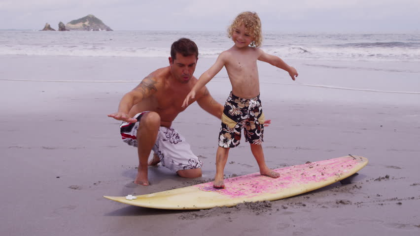 Father and son at beach with surfboard, Costa Rica