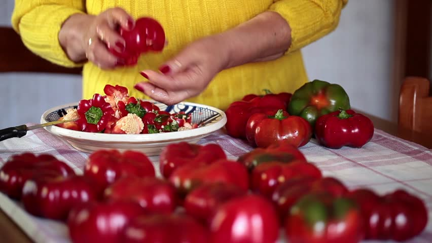 Footage of woman removing core and seeds to red tomato peppers.