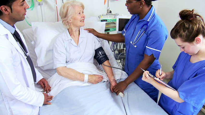 A Beautiful Female Nurse Attends To An Elderly Male ...