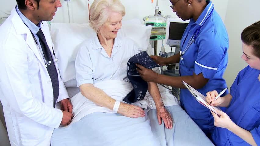 Elderly female patient having blood pressure taken at bedside by multi ethnic medical team #4761476