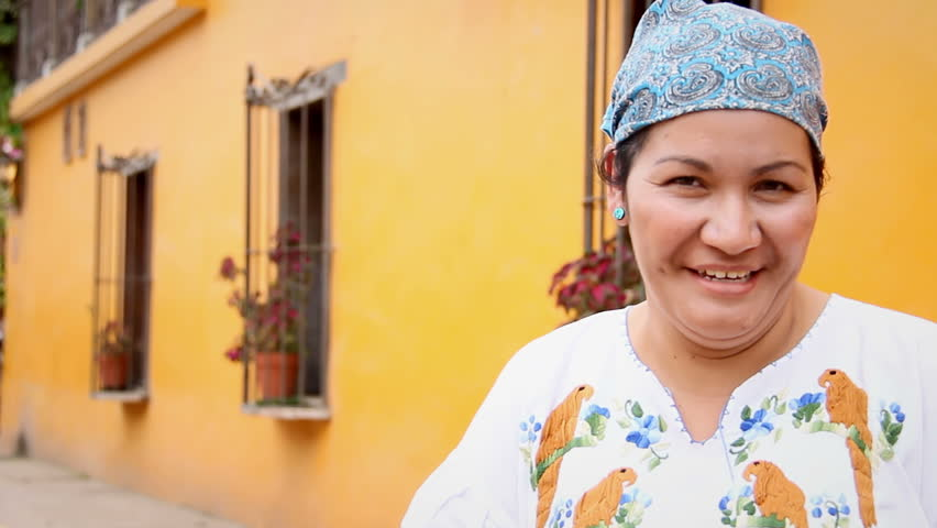 An older Mexican woman at a market smiles and poses for the camera