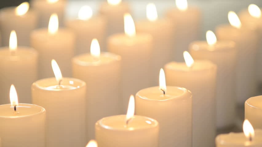 White Candles Burning Peacefully. One Candle In Focus, Other Candles Out Of