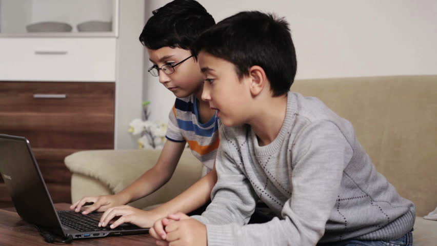 2 kids who are friends studying working looking at a website on a laptop computer playing video games and doing homework for school at home in the living room during the daytime