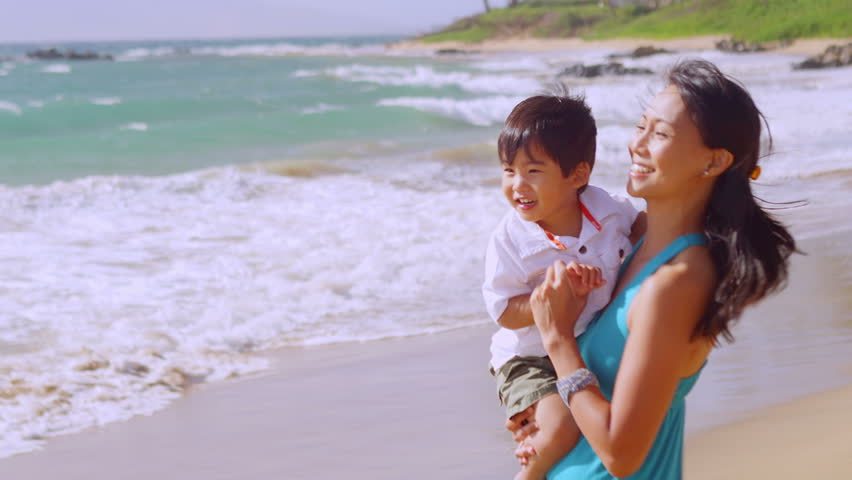 A mother holds her son in her arms as she stands at the edge of the water at the beach | Shutterstock HD Video #4776536