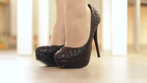 Woman comes into frame and take the high heels off. Close up. High definition video.