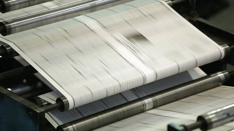 Close-up of metallic parts of the printing mechanism rolling freshly typed newspaper