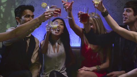 A group of attractive friends sit at a table in a club with drinks and toast each other
