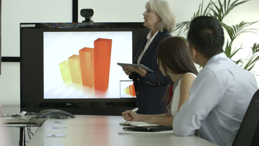 MS PAN Businesswoman explaining with the help of pie chart and digital tablet in board room