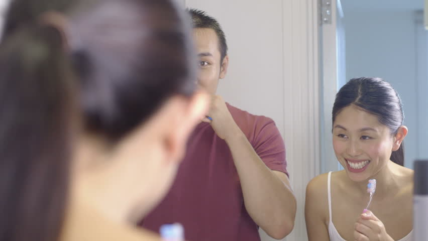 CU Young couple brushing teeth in bedroom