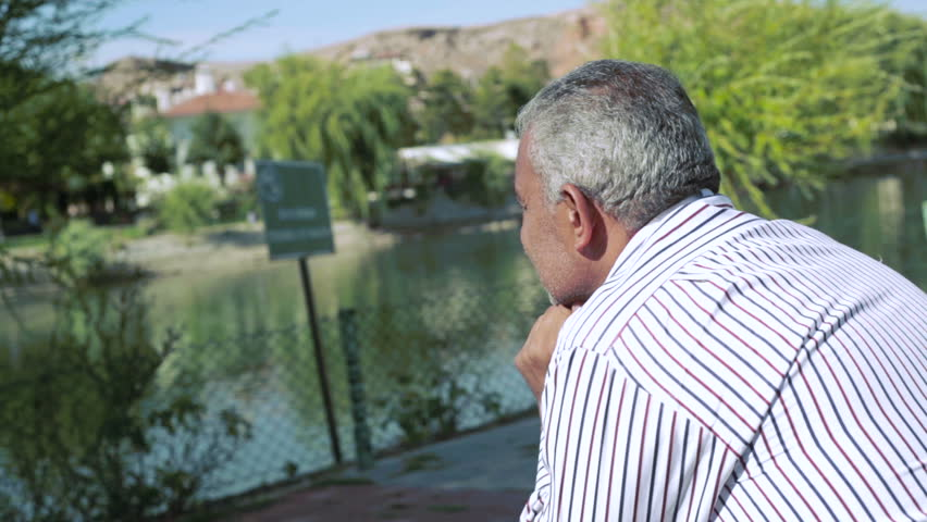middle aged man sitting on a bench in the park thinking and reflecting looking out onto a lake
