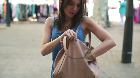 Woman in city searching cellphone in her bag