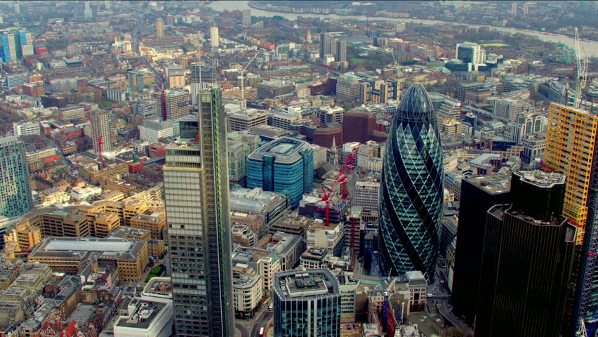 Dramatic aerial shot of the City of London financial district skyline. Features the Gherkin / 30 St Mary Axe building - shot then reveals Tower Bridge.