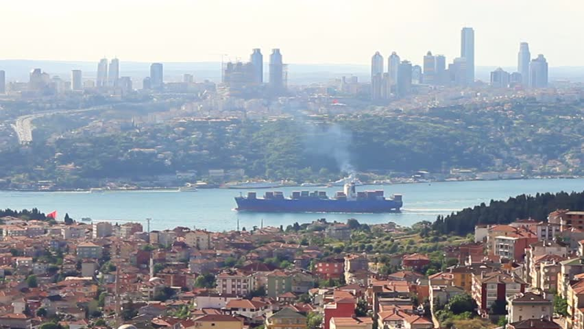 Istanbul in smog with a container ship passing in Bosporus. Zoom out, HD Video.