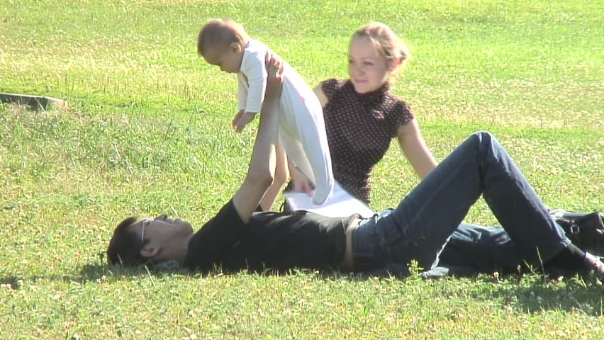 Happy family playing with baby on a grass