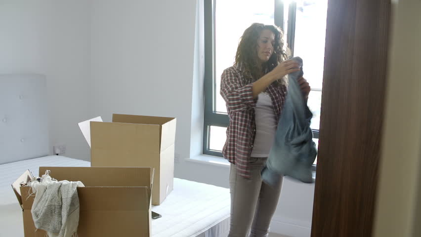 Young woman unpacking boxes and hanging up clothing in bedroom in new home | Shutterstock HD Video #4875956