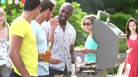 Young adult friends serving grilled meat and vegetables at backyard summertime barbecue