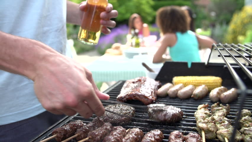 Close up of man food grilling on barbecue while women sit at backyard table and relax | Shutterstock HD Video #4879673