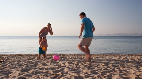 Young family frolicking together playing football soccer on the beach at sunset with the little boy running with his mother and father