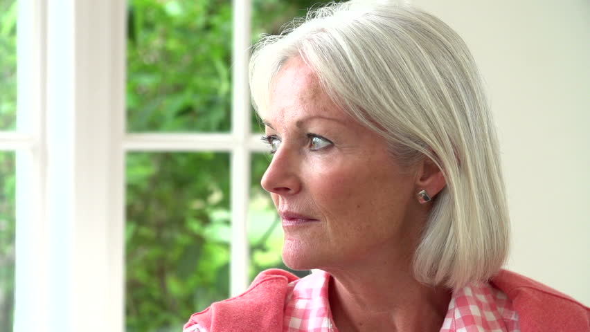 Close up portrait of middle aged woman turning to smile in slow motion