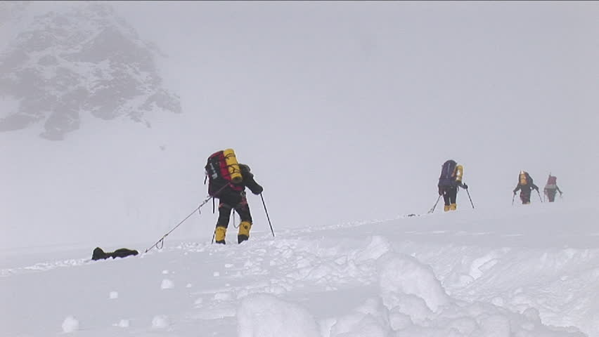 Snow falling on climbers as they struggle