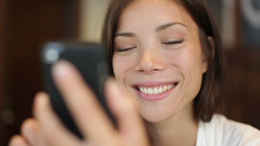 Smartphone girl using app on phone drinking coffee smiling in cafe. Beautiful multicultural young casual female professional on mobile phone. Mixed race Asian Caucasian model. | Shutterstock HD Video #4886240