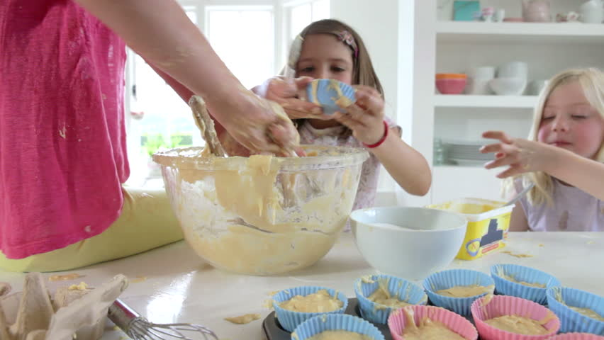Three Young Girls Spooning Cake Mixture Into Muffin Tin To Bake And Making  A Mess