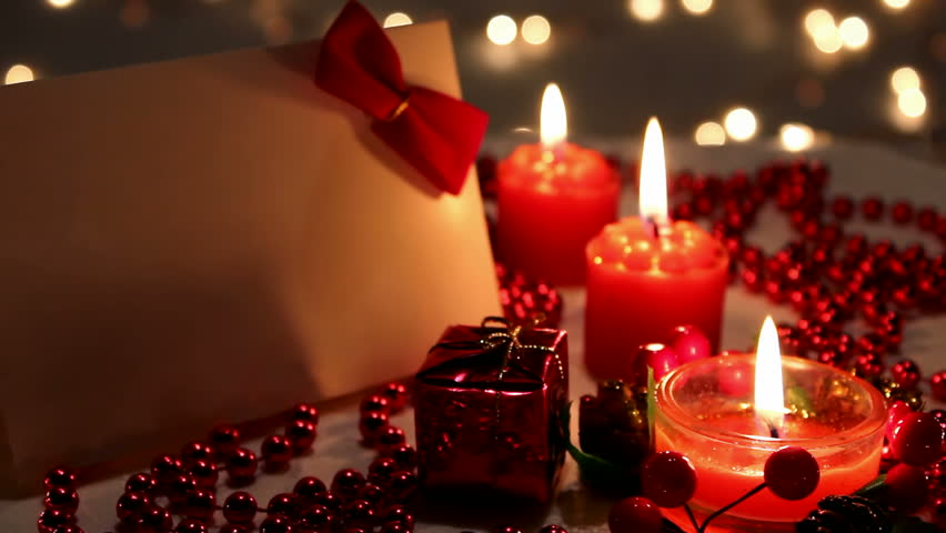 Christmas candles ; Christmas and New Year decoration with a lit candle and beautiful colorful ornaments with blurred background,video clip