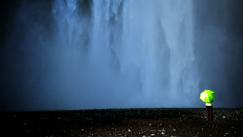 Concept shot of lone female standing on the edge of a waterfall with green umbrella to shelter from climate change 60 FPS | Shutterstock HD Video #489016