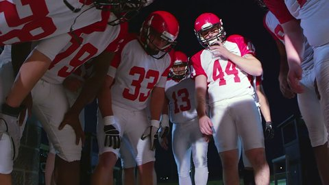 The camera looks up into a huddle full of football players talking before a play
