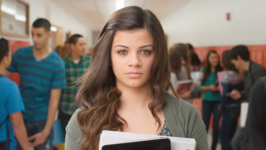 A female student holds her books to her chest and stares into the camera lens