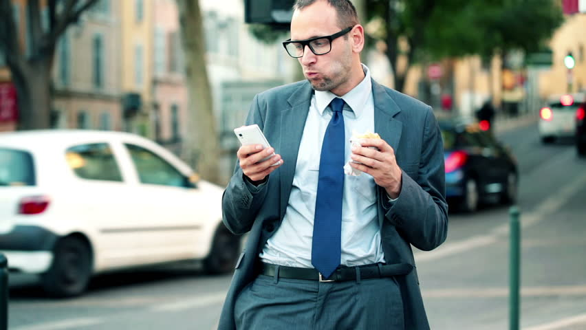 Businessman with smartphone eating sandwich by city street  | Shutterstock HD Video #4894526