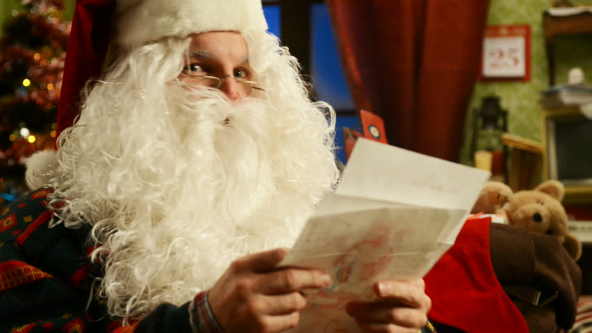 Santa Claus reading a letter at home