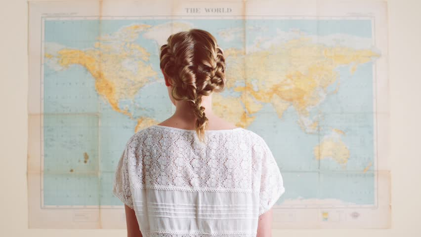 Tourist woman looking at world map planning travel adventure