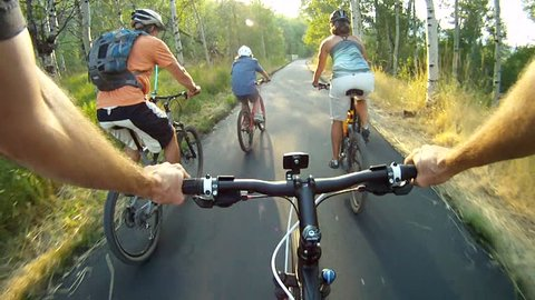 P.O.V, point-of-view of rider following a young family bike riding through tree-lined paved forest trail at sunset in Park City, Utah.